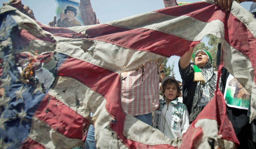 Protesters chant anti-U.S. slogans May 1 in front of the Gadhafi family compound in a residential area of Tripoli, Libya. (Associated Press)