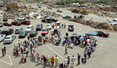ASSOCIATED PRESS With their church building destroyed by last week's tornado, members of Alberta Baptist Church in Tuscaloosa, Ala., gathered Sunday morning in the parking lot for a brief service before going out to help their neighbors. Many in this highly religious region saw God at work, even amid the devastation.