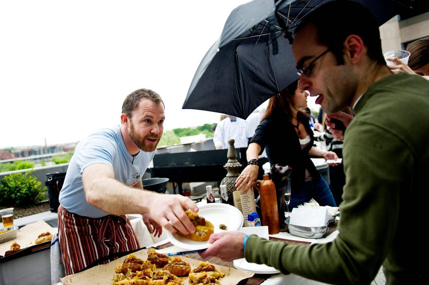 DREW ANGERER/THE WASHINGTON TIMES Dennis Marron, head chef at Jackson 20 Restaurant, serves a hickory-smoked half-smoke to a patron on the rooftop terrace of Domaso Restaurant. The winning entry in the friendly competition was Firefly restaurant on Dupont Circle with its fennel sausage and half-smoke bacon chili entry.