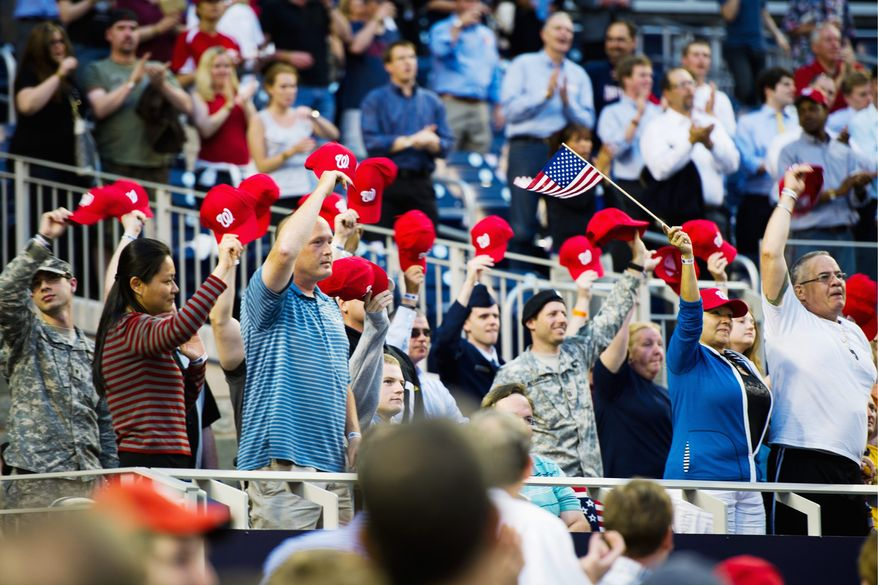 A flag and Nationals caps were waved by members of the military in acknowledge of the crowd's applause at Nationals Park.