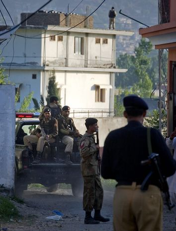 Pakistan army soldiers and a police officer patrol past the house (background) where al Qaeda leader Osama bin Laden was killed by U.S. forces on Sunday, ending a nearly 10-manhunt after the Sept. 11 attacks on U.S. soil. (Associated Press)