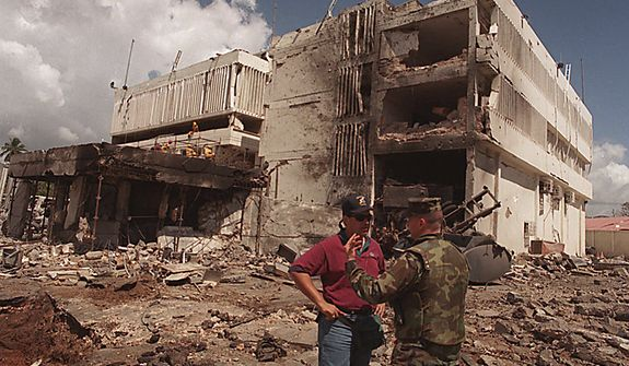 In this Aug. 15, 1998 file photo, a United States Marine talks with an FBI investigator in front of the damaged U.S. Embassy in the capital Dar es Salaam, Tanzania. Osama bin Laden, leader of the al-Qaida organization behind the Sept. 11, 2001 attacks against the United States and blamed for the 1998 embassy bombings in Kenya and Tanzania, is dead, a person familiar with the situation said late Sunday. (AP Photo/Brennan Linsley, File)