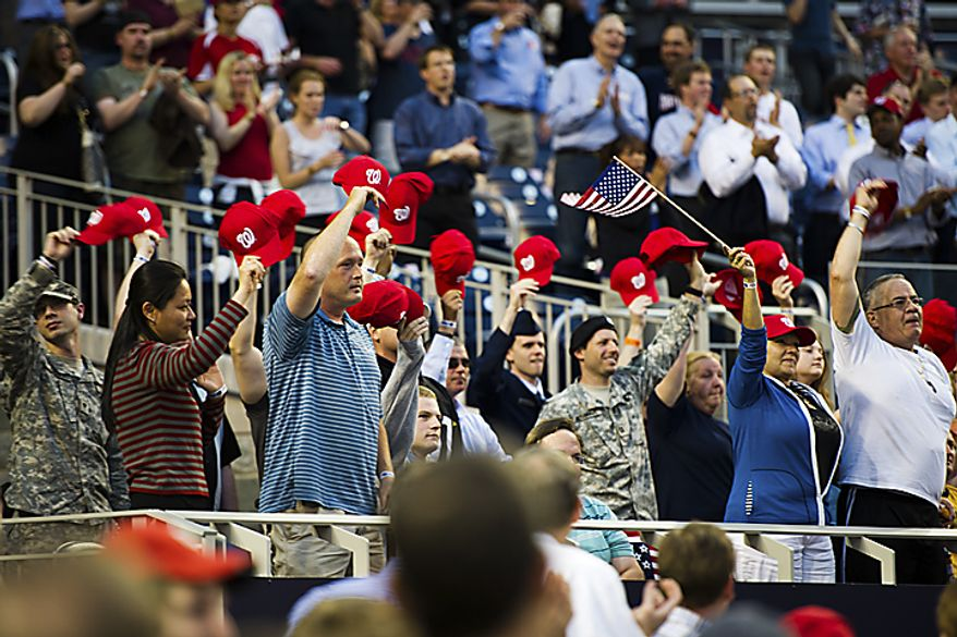Members of the military stand with Nats caps raised in the air as they acknowledge the crowd's standing ovation at Nationals Park for military service men and women during Military Appreciation Night at the park in Washington, D.C., Monday, May 2, 2011. (Drew Angerer/The Washington Times)