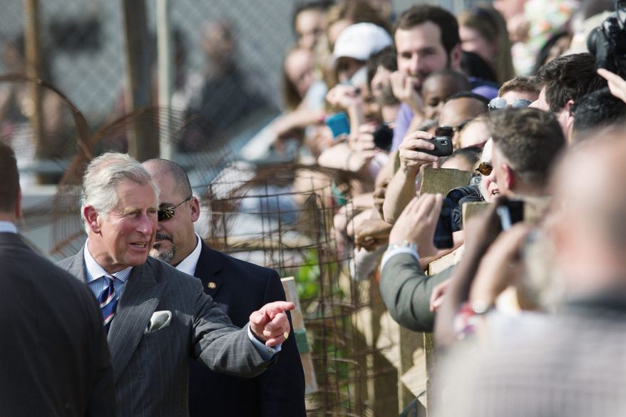 DREW ANGERER/THE WASHINGTON TIMES England's Prince Charles greets onlookers as he tours Common Good City Farm in Northwest on Tuesday. The mission of the farm is to build awareness of healthy, local, sustainable food systems.