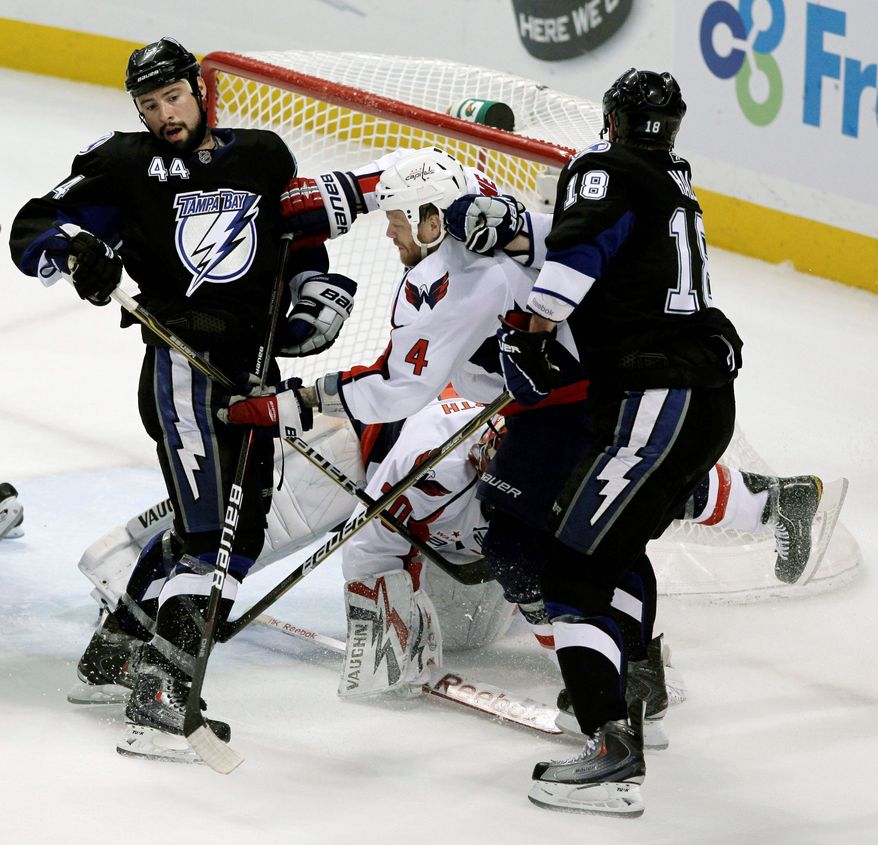 ASSOCIATED PRESS Tampa Bay's Nate Thompson (44) and Adam Hall put the squeeze on Washington defenseman John Erskine in front of the Capitals' goal during Game 3 of their Eastern Conference semifinal series Tuesday night in Tampa, Fla.