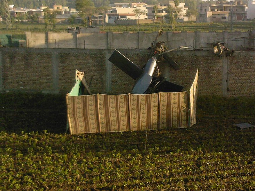 A photo taken by a resident of Abbottabad, Pakistan, on Monday, May 2, 2011, shows the wreckage of a U.S. helicopter next to the wall of the compound where, according to officials, Osama bin Laden was shot and killed in a firefight with U.S. forces. (AP Photo/Mohammad Zubair)