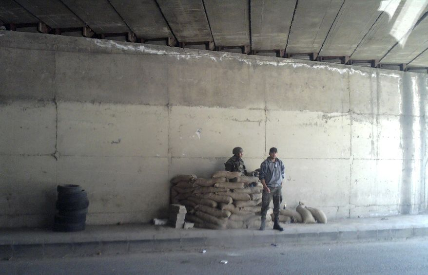 In this image made on a mobile phone from the window of a car, showing two Syrian soldiers at a checkpoint in a road tunnel in Damascus, Syria, Tuesday, May 3, 2011. Syrian authorities are thought to have detained more than 1,000 people in the latest sweep aimed at crushing the uprising against President Bashar Assad, a human rights group said Tuesday. (AP Photo)