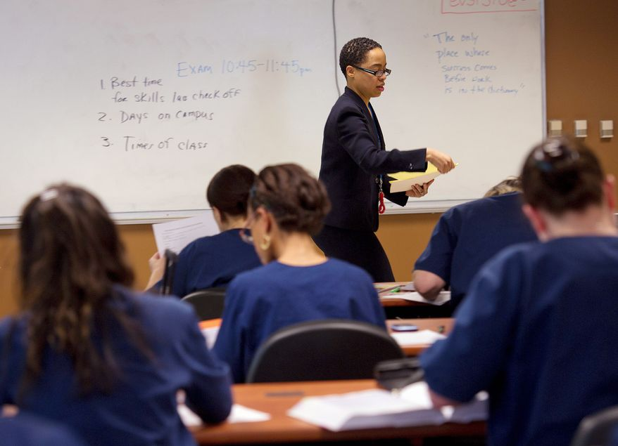 PHOTOGRAPHS BY BARBARA L. SALISBURY/THE WASHINGTON TIMES Ivy Dorsett, a nursing instructor at Everest College, hands out papers during class at the for-profit institution, which offers associate's degrees and diploma programs. About 350 students attend the McLean campus.
