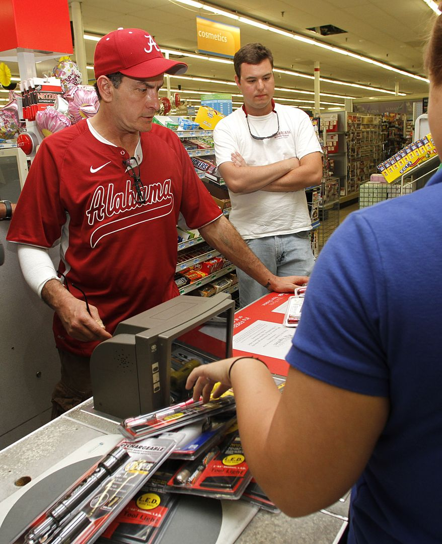 Actor Charlie Sheen (left) purchases flashlights with University of Alabama student David Harris at a local store in Tuscaloosa, Ala., on Monday. Sheen toured a neighborhood leveled by tornadoes and said Monday he wants to organize a relief event for victims in the state. (Associated Press)