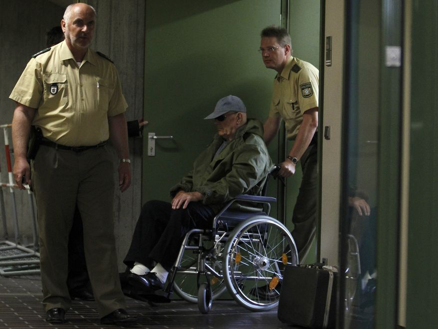 On Tuesday, May 3, 2011, Ukrainian-born John Demjanjuk arrives in a wheelchair at a Munich courthouse, where he is on trial on 28,060 counts of being an accessory to murder for allegedly serving as a guard in the Nazis' Sobibor death camp. (AP Photo/Matthias Schrader)