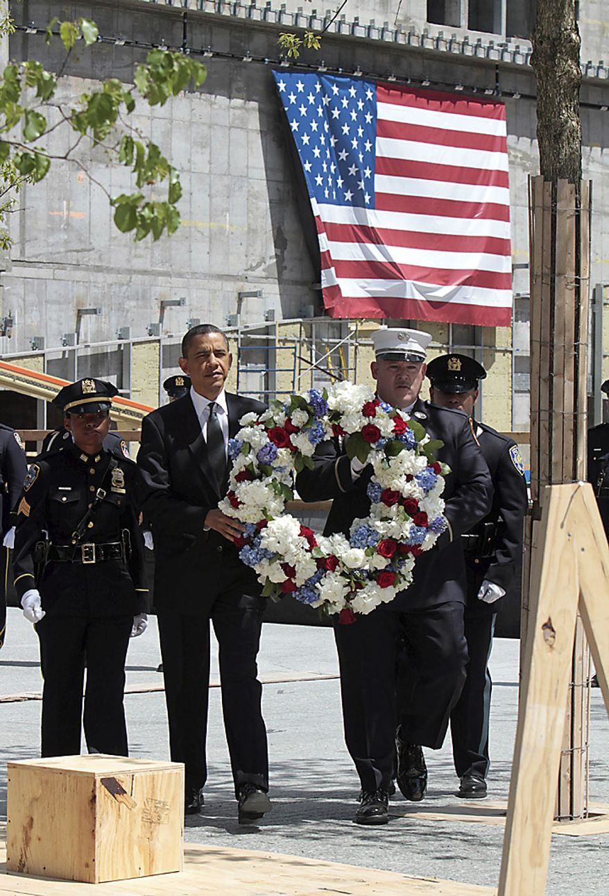 President Barack Obama, accompanied by a New York City Police officer, New York City Firefighter, and Port Authority officers, carries a wreath to be placed at the World Trade Center site, in New York,  Thursday, May 5, 2011. (AP Photo/Richard Drew)