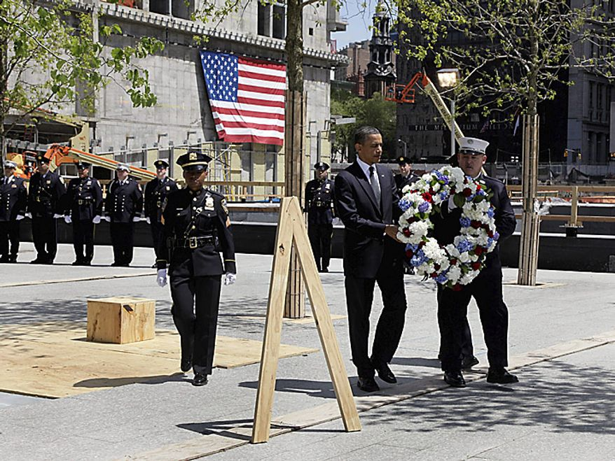 President Barack Obama and a New York City Fire Dept. lieutenant carry a wreath to be placed at the World Trade Center site, in New York,  Thursday, May 5, 2011. (AP Photo/Richard Drew)