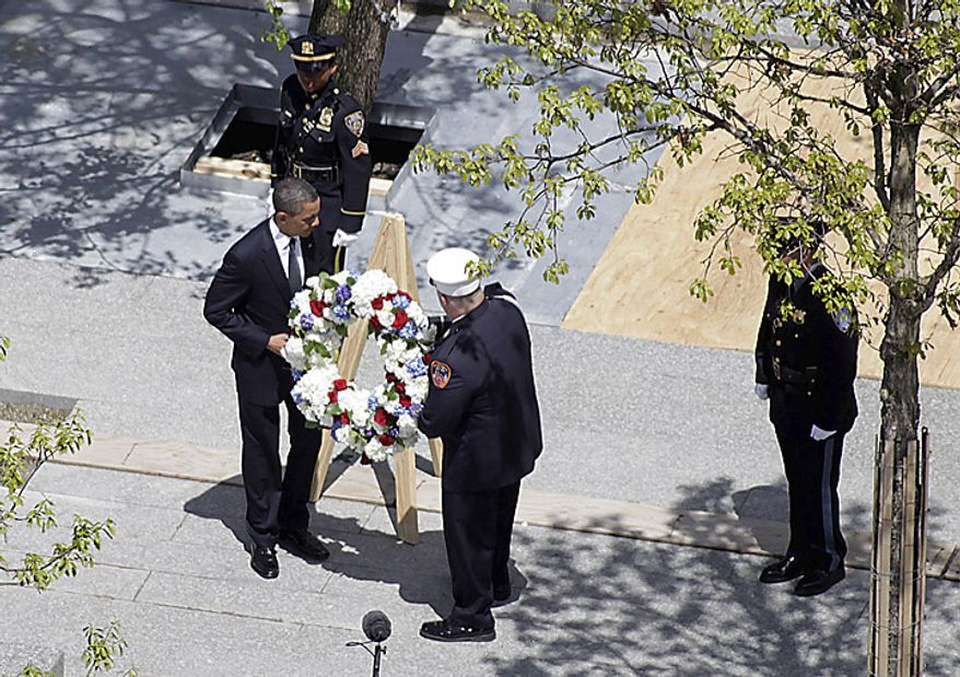 President Barack Obama and a New York City Fire Dept. lieutenant carry a wreath to be placed at the World Trade Center site, in New York,  Thursday, May 5, 2011.  (AP Photo/Seth Wenig)