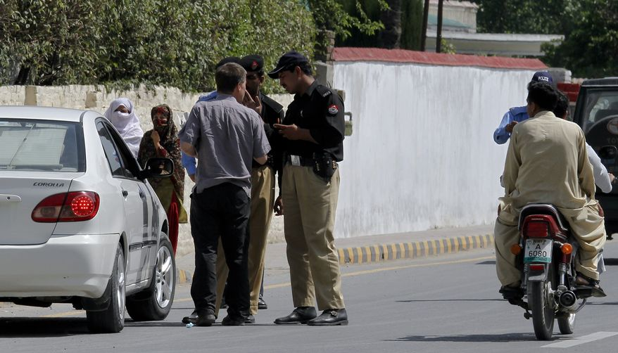 Pakistani police officers stop a foreign journalist on Wednesday, May 4, 2011, at a checkpoint on a road leading to the compound where al Qaeda leader Osama bin Laden was caught and killed in Abbottabad, Pakistan. The residents of Abbottabad still are confused and suspicious about the killing of bin Laden, which took place in their midst before dawn Monday. (AP Photo/Anjum Naveed)