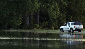 A driver tries Thursday to drive on a submerged portion of Mississippi Highway 465 on his way to Eagle Lake, near Vicksburg, Miss., before rising flood waters stopped him. Residents along Mississippi River tributaries are evacuating ahead of the possible record flooding. (Associated Press)