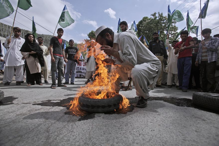 A supporter of a Pakistani religious group Jamaat-e-Islami burns a tire during an anti-American rally Friday in Abbottabad, Pakistan. Osama bin Laden was killed by a helicopter-borne U.S. military force on Monday, in a fortress-like compound on the outskirts of Abbottabad. (Associated Press)