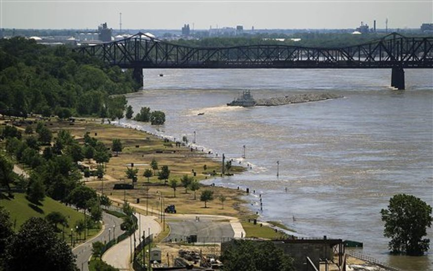 A tugboat heads under the Harahan Bridge in Memphis, Tenn., next to Tom Lee Park which is beginning to be flooded by the Mississippi River on Friday, May 6, 2011. Memphis Police began distributing more than 1,000 evacuation notices to area homeowners on Friday. (AP Photo/Lance Murphey)