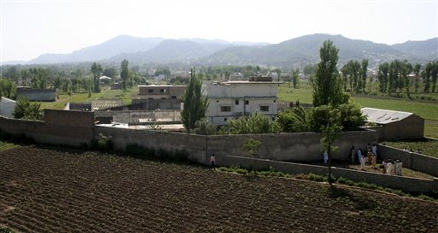 FILE - This May 3, 2011 file photo shows a view of Osama bin Laden's compound in Abbottabad, Pakistan, the day after a U.S. military raid that ended with the death of the al-Qaida leader Osama bin Laden. Holed up in the compound, bin Laden was scheming how to hit the United States hard again, according to newly uncovered documents that show al-Qaida plans for derailing an American train on the upcoming 10th anniversary of the 9/11 attacks. (AP Photo/Aqeel Ahmed, File)
