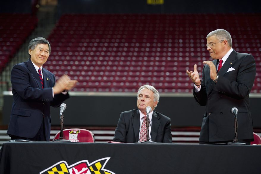 ** FILE ** University of Maryland president Wallace D. Loh (left) and director of athletics Kevin Anderson (right) applauded an emotional Gary Williams during the news conference when Williams officially announced his retirement as the school's basketball coach after nearly 22 years. (Barbara L. Salisbury/The Washington Times)