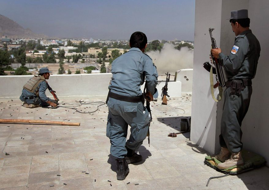 ASSOCIATED PRESS An Afghan policeman runs to take up a position Sunday on a rooftop against Taliban fighters hiding in a government building from which smoke is rising in Kandahar on the second day of a major assault.