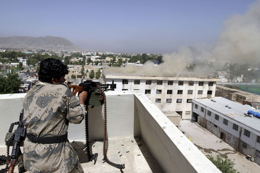 An Afghan border policeman fires on Taliban fighters hidden in the Traffic Department building, where smoke rises from the rooftop, in Kandahar, Afghanistan, on Sunday, May 8, 2011. The Taliban unleashed a major assault Saturday on government buildings throughout Kandahar, Afghanistan's main southern city, an attack that cast doubt on how successful the U.S.-led coalition has been in its nearly yearlong military campaign to establish security and stability in the former Taliban stronghold. (AP Photo/Allauddin Khan)