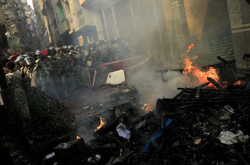 Egyptian army forces guard burned furniture from a building belonging to Christians that was set afire during clashes between Muslims and Christians in the Imbaba neighborhood of Cairo on Sunday, May 8, 2011. (AP Photo/Khalil Hamra)