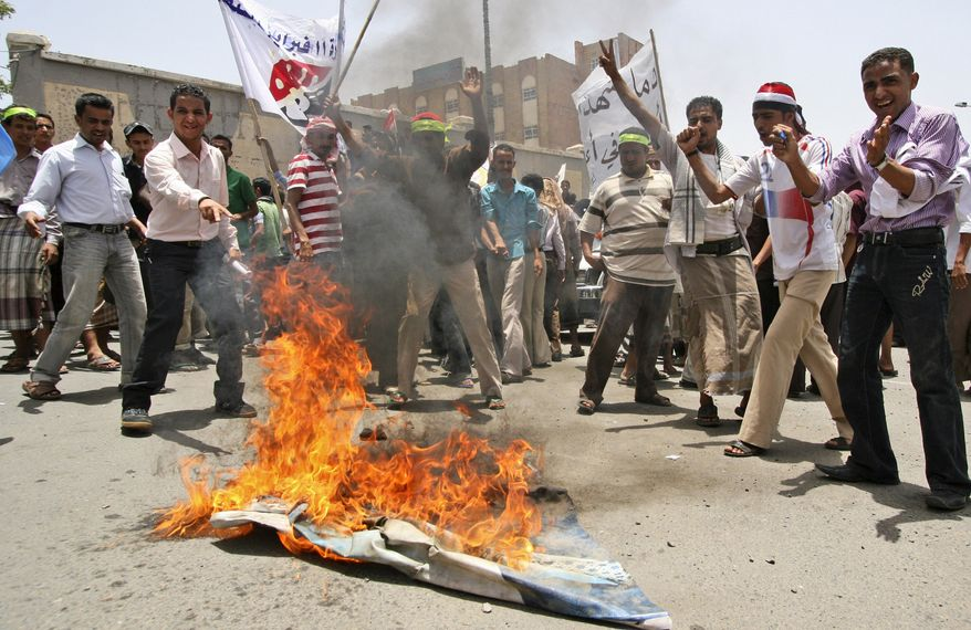 Anti-government protesters burn a poster showing Yemeni President Ali Abdullah Saleh during a demonstration Sunday demanding the resignation of Saleh in Taiz, Yemen. Security forces backed by army units opened fire Sunday on protesters demanding the ousting of Yemen's longtime president, killing three, an opposition activist said. (Associated Press)