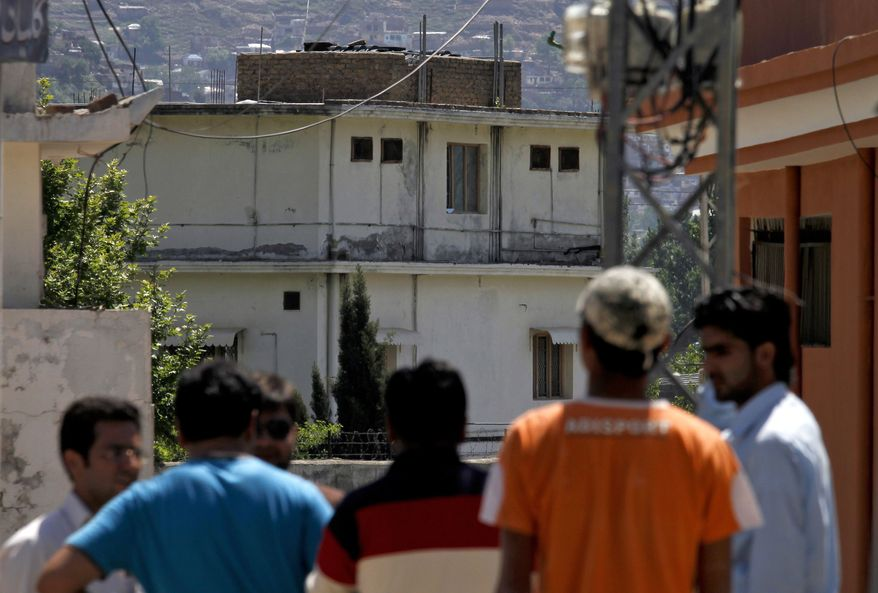 Pakistani youths view the house (background) of former al Qaeda leader Osama bin Laden in Abbottabad, Pakistan, on Sunday, May 8, 2011. Bin Laden was killed by a helicopter-borne U.S. military force last Monday in the fortresslike compound. (AP Photo/Anjum Naveed)