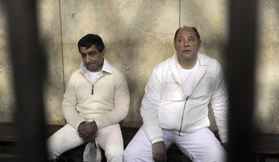 ** FILE ** Former Egyptian Tourism Minister Zuheir Garana (right) and steel tycoon and prominent ruling party leader Ahmed Ezz, wearing white prison uniforms, sit in a metal cage as they appear in criminal court in Cairo on Thursday, Feb. 24, 2011. The court has convicted Garana of corruption for allowing two businessmen to illegally acquire state land and has sentenced him to five years in prison. (AP Photo, File)