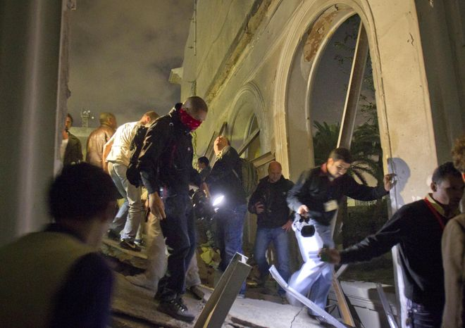 In this photo taken on a government-organized tour, Libyan government officials and the media move through the ruins of an official building following a NATO airstrike in Tripoli, Libya, early on Tuesday, May 10, 2011. (AP Photo/Darko Bandic)