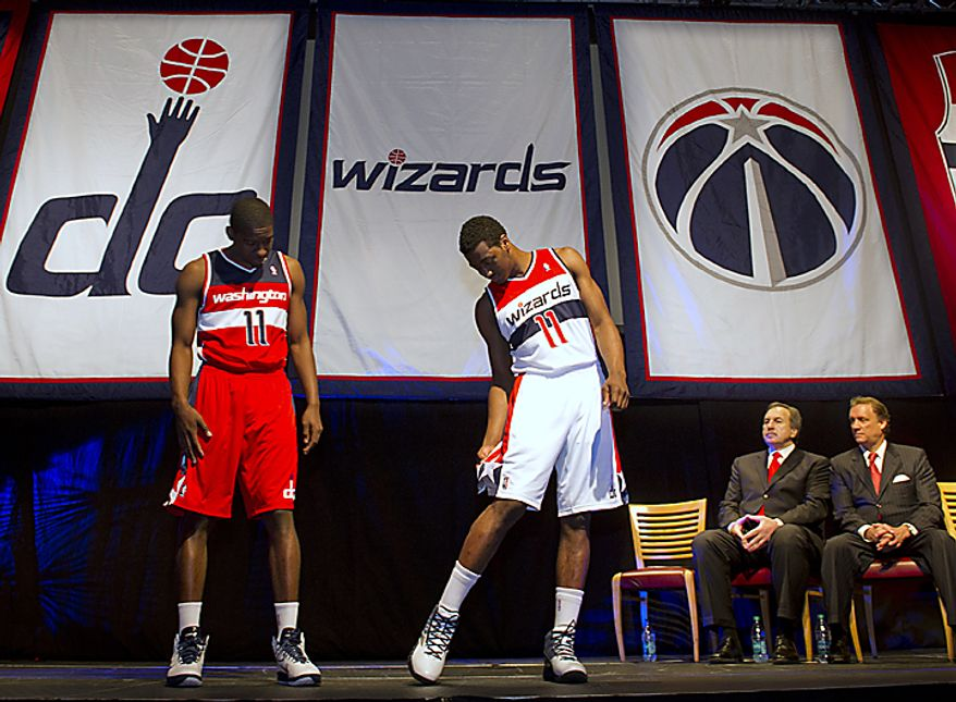** FILE ** The Washington Wizards' Jordan Crawford (left) and John Wall (second from left) check out the team's new uniforms while Wizards President Ernie Grunfeld (second from right) and head coach Flip Saunders look on at the Verizon Center in Washington on Tuesday, May 10, 2011. (Rod Lamkey Jr./The Washington Times)
