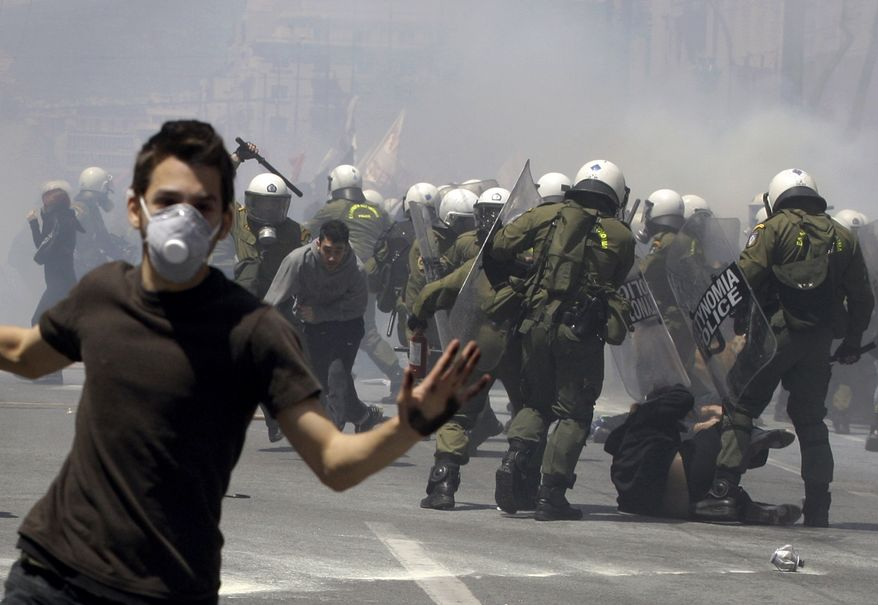 A young protester runs as others are hit by riot police during clashes Wednesday in Athens. Riot police made heavy use of tear gas and stun grenades to disperse youths throwing stones and petrol bombs during a march attended by 20,000 people to protest the Greek government's harsh austerity measures. (Associated Press)
