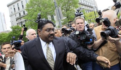 Raj Rajaratnam, billionaire co-founder of Galleon Group, is surrounded by photographers Wednesday as he leaves Manhattan federal court in New York. The former Wall Street titan was convicted Wednesday of making a fortune by coaxing a crew of corporate tipsters to give him an illegal edge on blockbuster trades in technology and other stocks, in what prosecutors called the largest insider trading case ever involving hedge funds. (Associated Press)