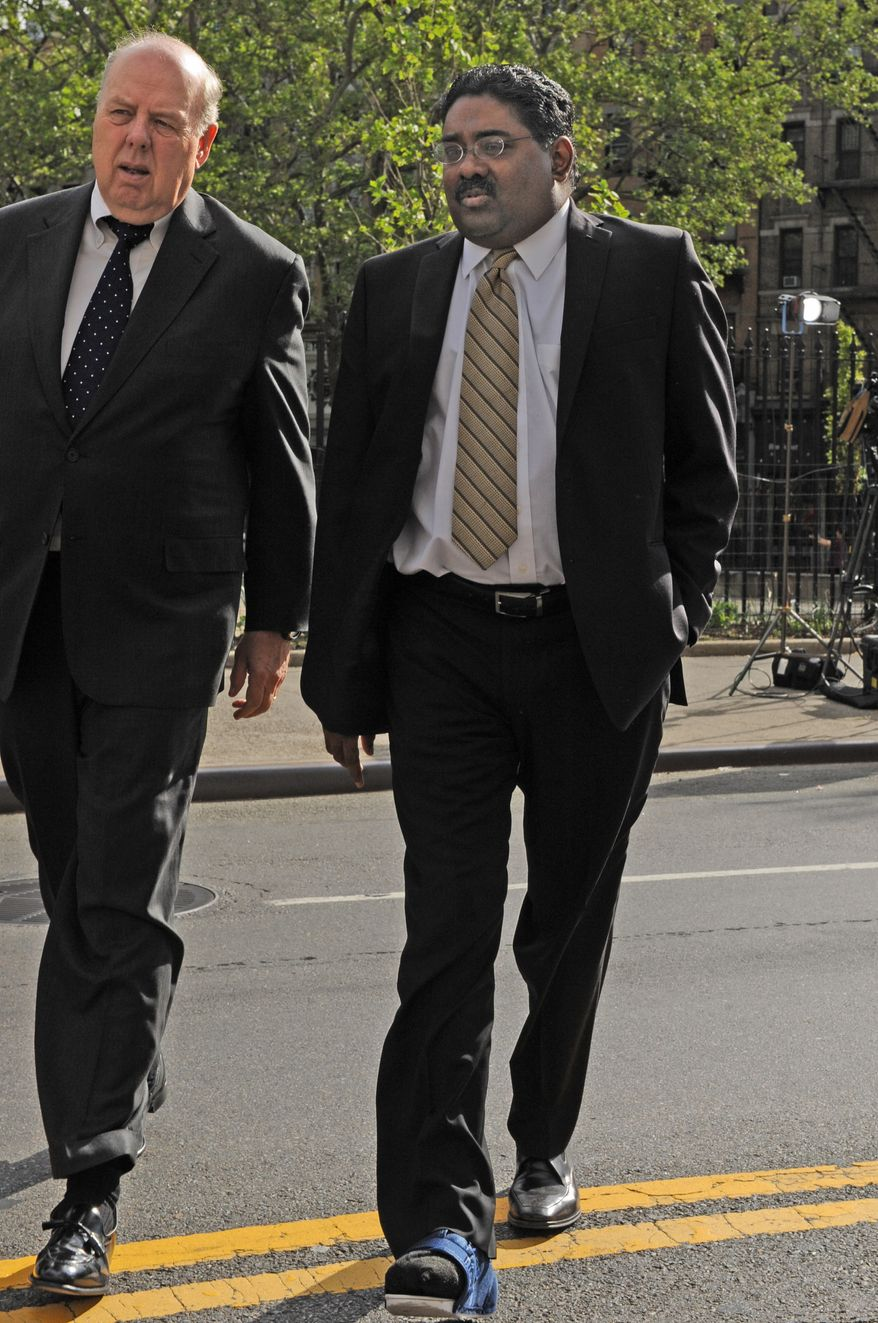 Wearing a medical boot from foot surgery, billionaire co-founder of Galleon Group Raj Rajaratnam (right) enters Manhattan federal court Wednesday with his attorney, John Dowd, in New York. Jury deliberations entered a third week Wednesday with Rajaratnam facing insider trading and conspiracy charges accused of gaining $63 million trading on illegal stock tips. (Associated Press)