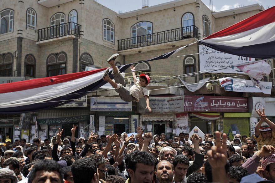 A Yemeni boy is thrown into the air by anti-government protesters during a demonstration demanding the resignation of Yemeni President Ali Abdullah Saleh in Sanaa, Yemen, on Tuesday, May 10, 2011. (AP Photo/Hani Mohammed)
