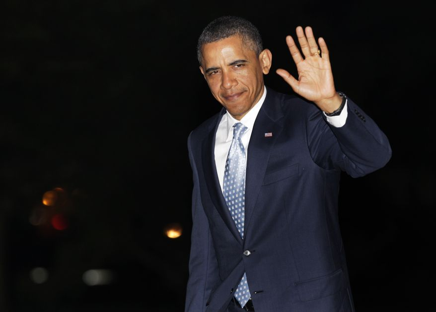 President Obama waves to media Wednesday while walking from Marine One to the White House upon his return from Texas. (Associated Press)