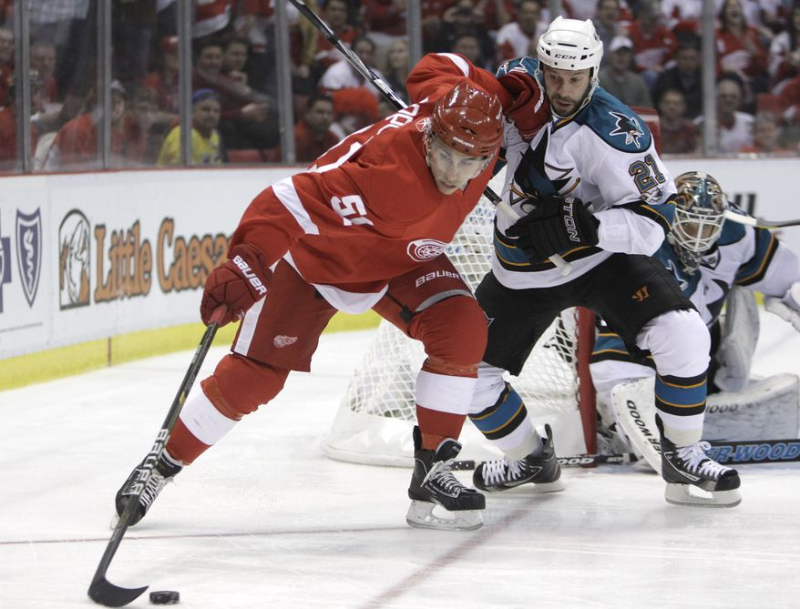 Detroit Red Wings center Valtteri Filppula (51) of Finland, defended by San Jose Sharks center Scott Nichol (21) plays the puck behind goalie Antti Niemi during the first period in Game 6 of a second-round NHL Stanley Cup playoffs hockey game in Detroit, Tuesday, May 10, 2011. (AP Photo/Carlos Osorio)