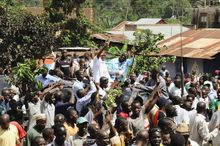 Kizza Besigye (background center right) waves to supporters beside his wife Winnie Byayima (left) as he returns from Nairobi after medical treatment on the day of the inauguration of his longtime political rival, President Yoweri Museveni. (Associated Press