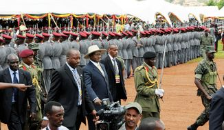 Ugandan President Yoweri Museveni (center, wearing a hat) inspects a guard after being sworn in as president at Kololo Airstrip in the capital city of Kampala on May 12, 2011. Mr. Museveni is starting a fourth term that will extend his rule to 30 years. (Associated Press)