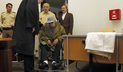 Lawyer Ulrich Busch (foreground) greets his client John Demjanjuk, who was convicted in a Munich court of thousands of counts of acting as an accessory to murder at a Nazi death camp and sentenced to five years in prison on Thursday, May 12, 2011. (AP Photo/Matthias Schrader)