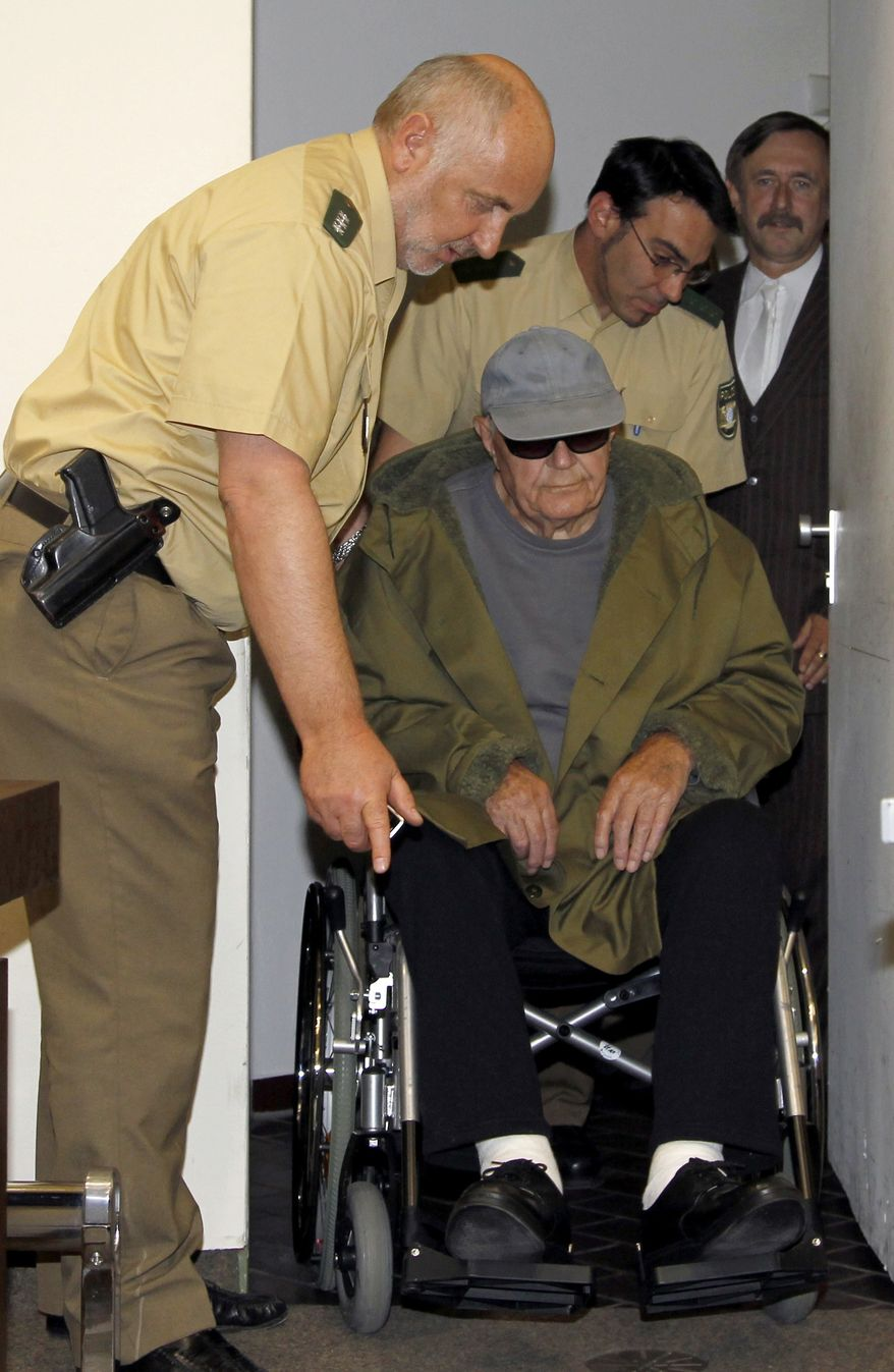 John Demjanjuk arrives in his wheelchair at the court building in Munich, southern Germany, on Thursday, May 12, 2011. (AP Photo/Matthias Schrader)