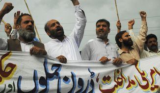 """**FILE** Supporters of the Pakistani religious party Jamaat-e-Islami rally in Rawalpindi, Pakistan, on May 6 to condemn the killing of al Qaeda leader Osama bin Laden and U.S. drone attacks on Pakistani tribal areas. The banner reads, """"We condemn U.S. interference and drone attacks."""" (Associated Press)"""