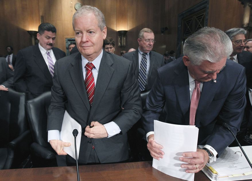 ConocoPhillips CEO James Mulva (left) and ExxonMobil CEO Rex Tillerson gather their things on Capitol Hill in Washington on Thursday, May 12, 2011, after testifying before the Senate Finance Committee. (AP Photo/Alex Brandon)