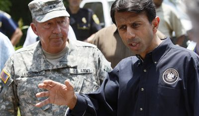 Louisiana Gov. Bobby Jindal (right) speaks with workers Thursday while viewing levee construction work with Maj. Gen. Bennett Landreneau, adjutant general of the Louisiana National Guard, in Krotz Springs, La., during a tour of areas that may be affected by flooding if the Morganza Spillway north of Baton Rouge is opened. (Associated Press)