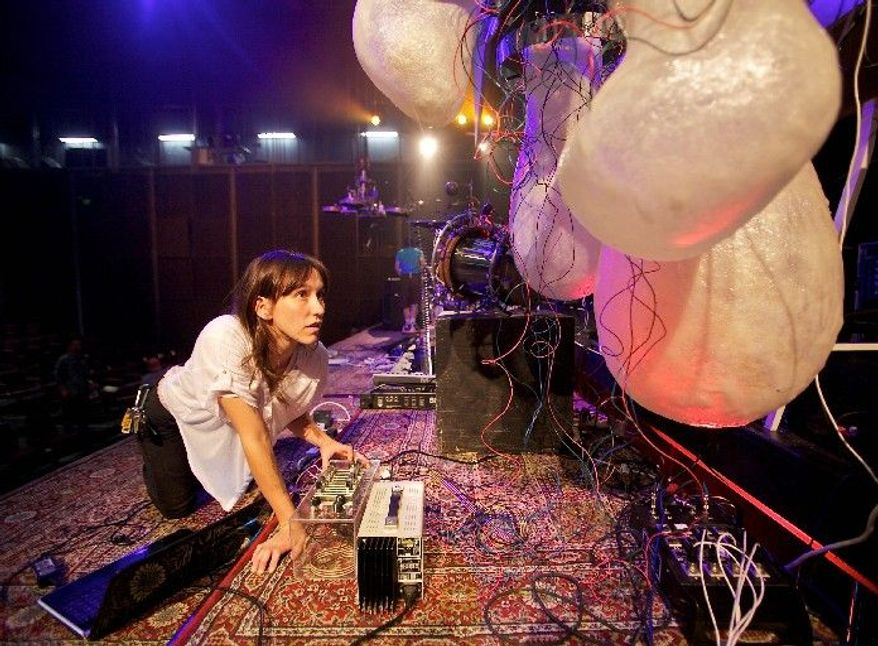 "ASSOCIATED PRESS PHOTOGRAPHS Lizzie Eggart, a student at the California Institute of the Arts, works on the Egg Babies lighting robot, part of the school's KarmetiK Machine Orchestra. ""Depending on what kind of note it is - bass, high note, treble - it will respond with a color,"" Ms. Eggert explained."