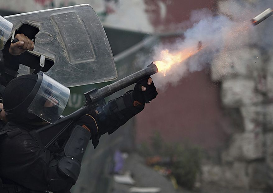 An Israeli police officer fires tear gas at Palestinian protesters, not seen, during clashes in the east Jerusalem neighborhood of Issawiyeh, Sunday, May 15, 2011. Israeli troops clashed with Arab protesters along three hostile borders on Sunday, leaving as many as 12 people dead and dozens wounded (...)