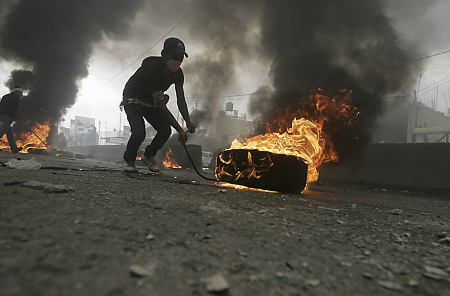 "A Palestinian protestor stands next to a burning barricade blocking the road during clashes with Israeli troops, not seen,  following a demonstration to mark the 63rd anniversary of ""Nakba"", Arabic for ""Catastrophe"", the term used to mark the events leading to Israel's founding in 1948, in the Qalan(...)"