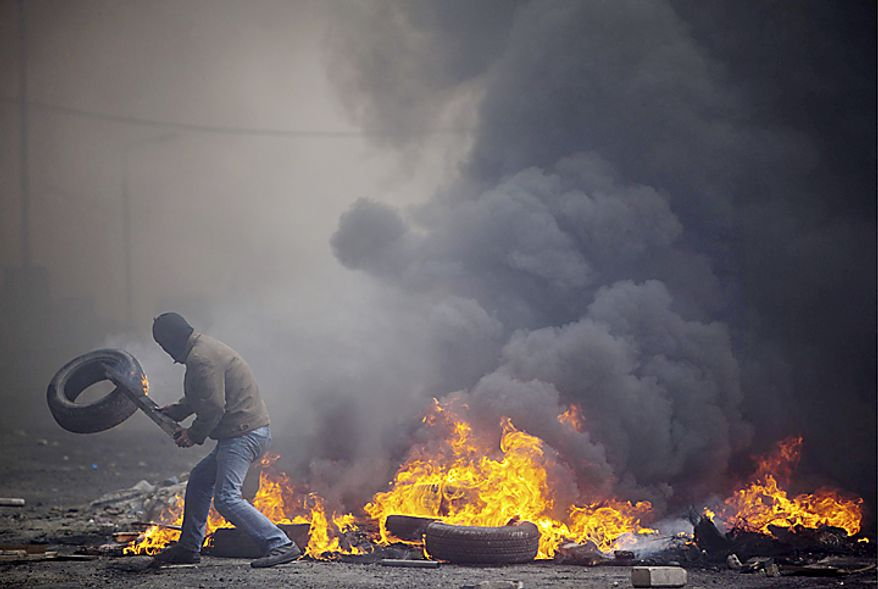 "A Palestinian protester adds a tire to a burning barricade blocking the road during clashes with Israeli troops, not seen, following a demonstration to mark the 63rd anniversary of ""Nakba"", Arabic for ""Catastrophe"", the term used to mark the events leading to Israel's founding in 1948, in the Shuafa(...)"