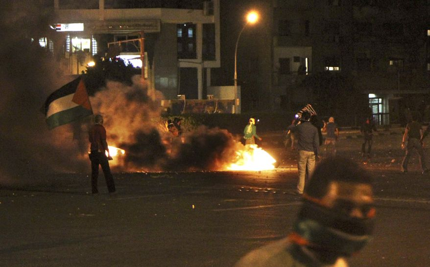 Pro-Palestinian demonstrators clash Sunday with Egyptian riot police near the Israeli embassy in Cairo, Egypt. (Associated Press)