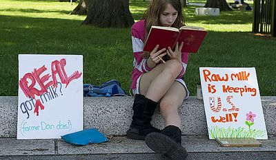 Fourteen-year-old Audrey Sarwer of Annapolis, Md., reads a book while sitting next to signs about raw milk at the Grassfed on the Hill rally at Upper Senate Park in Washington, D.C., on Monday, May 16, 2011. Her family gets fresh milk from Pennsylvania Amish dairy farmer Dan Allgyer, who was the subject of an FDA sting operation. The rally included samples of fresh milk, and Morgan the cow was also milked on site. (Barbara L. Salisbury/The Washington Times)